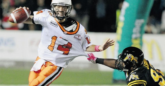 Travis Lulay avoids a Hamilton tackler. - Photo: Canadian Press, Post Media News